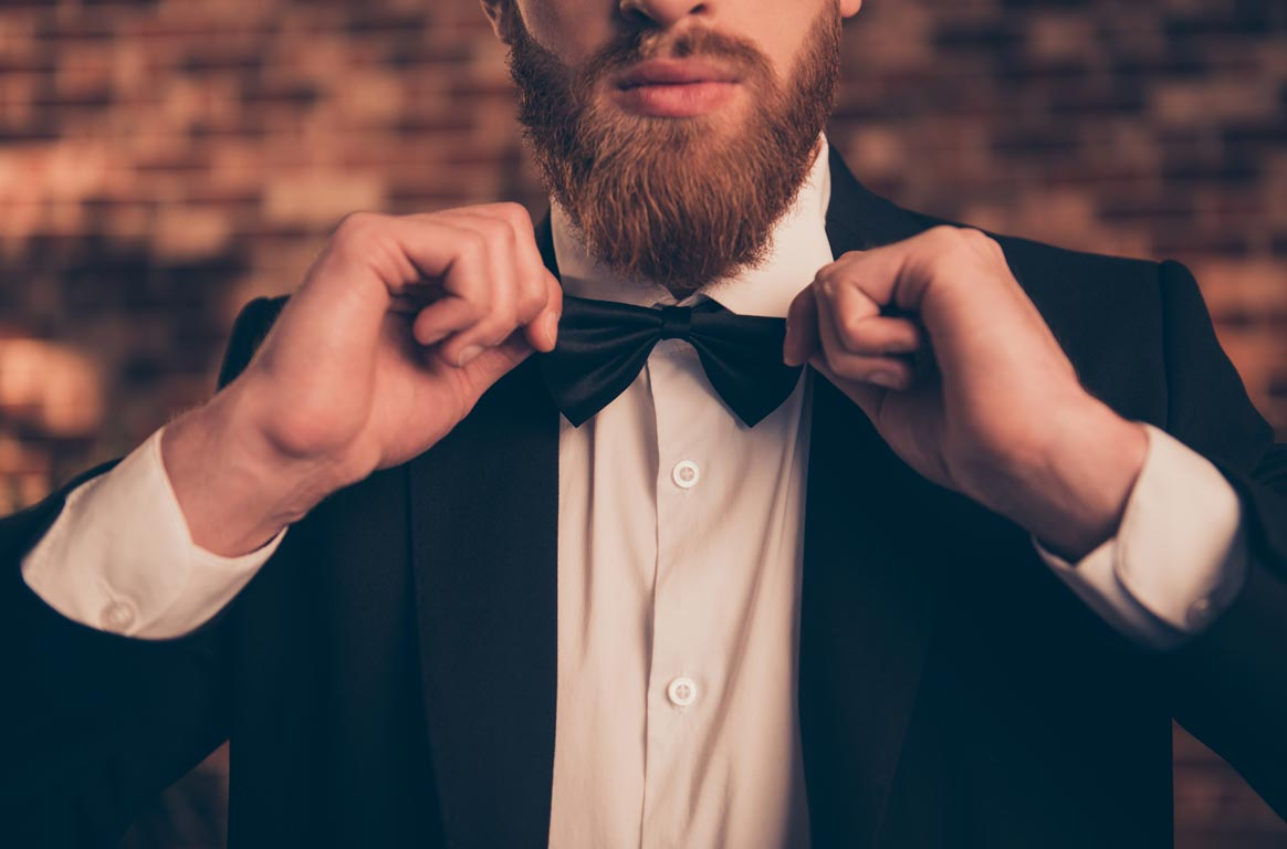 Close up half-faced portrait of handsome confident attractive serious guy fixing bowtie at corporate event organized by Spa Tours Bulgaria