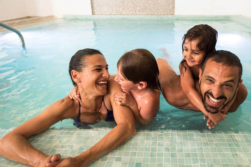 Woman and man laughing with their two children in a swimming pool during the International Jazz Festival in Bansko