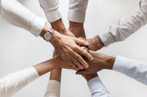 Group of different hands touching each other in a corporate event