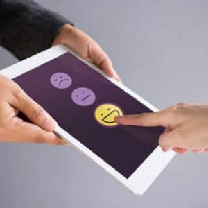 Women's finger touching a smile face on a tablet