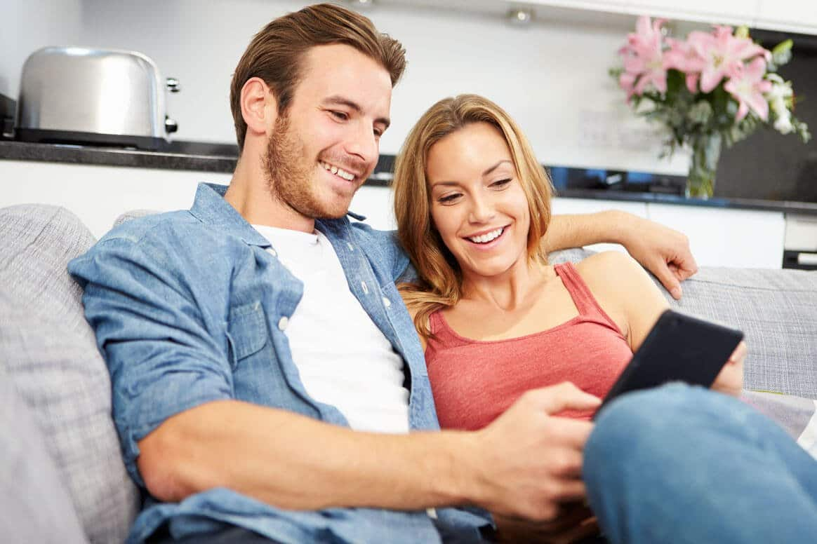 Young couple sitting on sofa searching offers with digital tablet