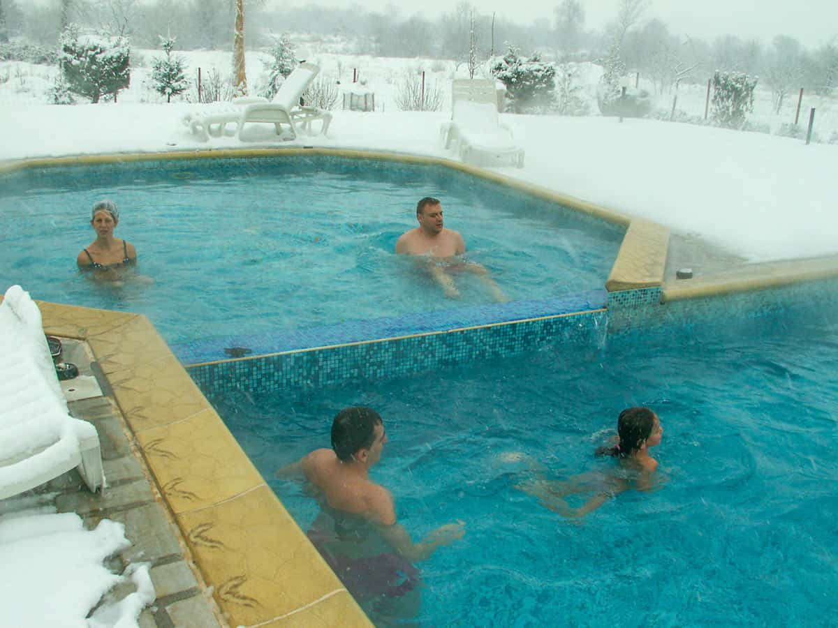 Outdoor swimming pool with 4 people enjoying the hot springs of Dolna Banya during the winter in Bulgaria
