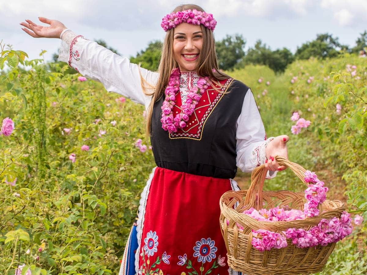 Bulgarian girl dressed in traditional dress saying welcome during the Annual Rose Festival in Kazanlak, Bulgaria