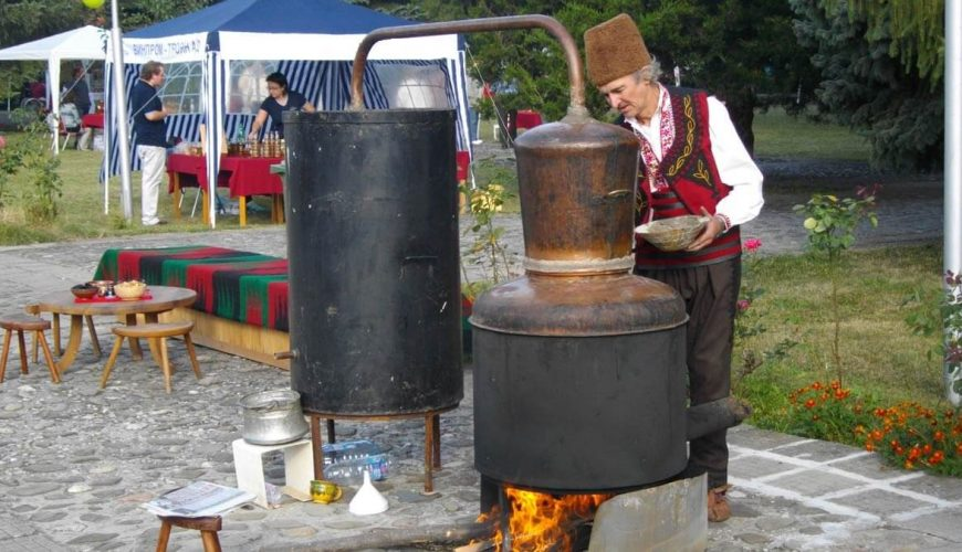 Old man dressed in folklore costumes preparing home-made rakia during the Bulgarian Plum Festival