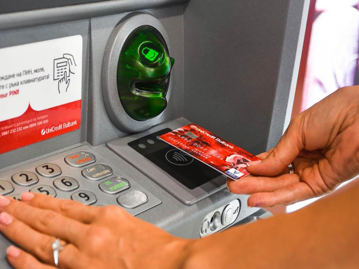 Bulgarian woman with silver ring put her debit card visa at Atm in Bulgaria