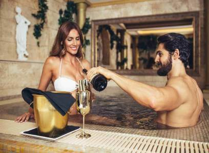 Man and woman drinking bottle of wine in Jacuzzi. Typical example what are tailor made holidays in Bulgaria