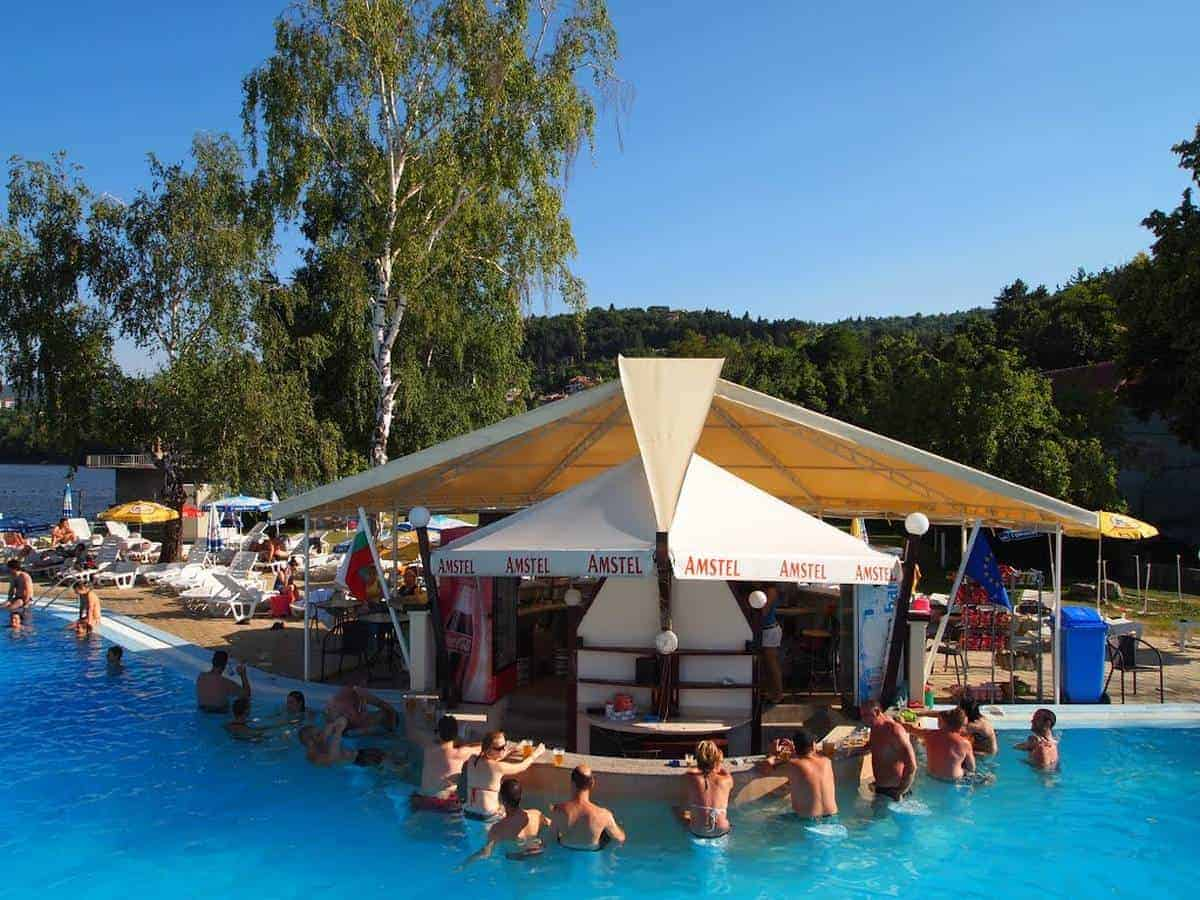 People enjoying a swimming pool with a water bar in Pancharevo, Sofia. They visit the pool during their private tours in Sofia.